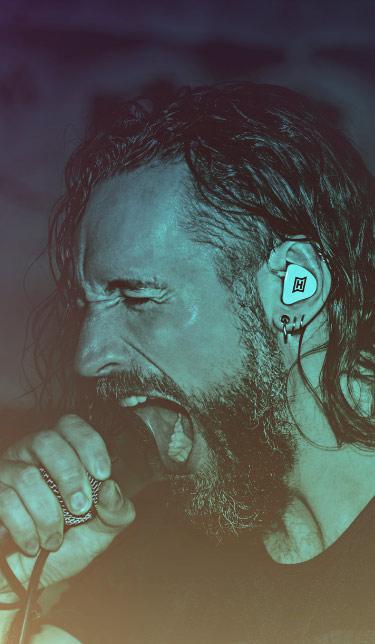 Professionelles In Ear Monitoring für Live-Auftritte – dieser Sänger einer Band rockt die Bühne mit HEAROS In Ears in den Ohren.